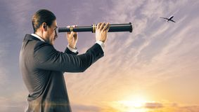 Travel and future concept. Side view of young caucasian businessman using telescope on beautiful bright sky background with airplane. Travel and future concept stock photo