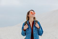 Travel girl with backpack in a sunglasses on a sand beach royalty free stock photos