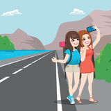 Travel Girl Friends Hitchhiking. Two young girl friends on travel making selfie with hitchhiking pose on roadside Royalty Free Stock Image
