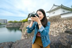 Travel girl sitting and taking pictures. Happy travel girl sitting and taking pictures of the scenary of osaka castle with a excting smile royalty free stock images