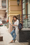 Travel girl standing in the street looking in newspaper. Royalty Free Stock Photography
