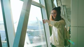 Travel girl stands at the window in airport terminal stock video footage