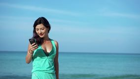 Travel girl taking selfie on the phone on the beach. Travel girl wearing dress using a smart phone on summer holidays on the beach stock footage