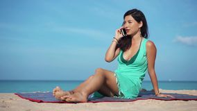 Travel girl talking to the phone on the beach stock footage