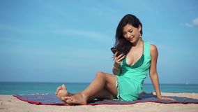 Travel girl ussing app on the phone on the beach. Travel girl wearing dress using a smart phone on summer holidays on the beach stock footage