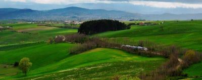Travel through green hills. Modern train travelling through green hills royalty free stock image
