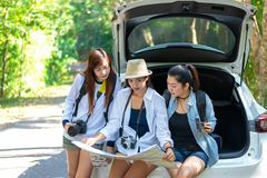Travel group asian woman traveler sitting on hatchback car for trip road with outdoors forest in vacations and holiday trips. stock photos