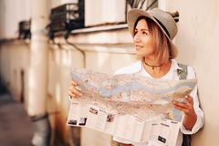 Travel guide. Young female traveler with backpack and with map on the street. Travel concept Royalty Free Stock Photography