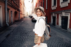 Travel guide. Young female traveler with backpack and with map on the street. Travel concept Royalty Free Stock Photo