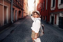 Travel guide. Young female traveler with backpack and with map on the street. Travel concept Royalty Free Stock Images