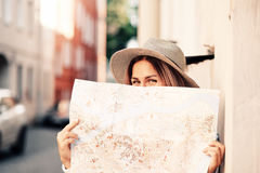 Travel guide. Young female traveler with backpack and with map on the street. Travel concept Royalty Free Stock Image