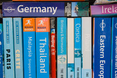Travel guides. A collection of Lonely Planet and Rough Guide travel guides on someones bookshelf stock photos
