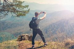 Travel guy standing on top of the mountain and takes pictures of the smartphone View from back of the tourist traveler. On background mountain Royalty Free Stock Images