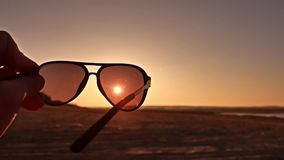 Travel. Hand holds sunglasses at sunset lifestyle nature stock video