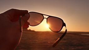Travel. Hand holds sunglasses at sunset nature lifestyle. Travel. Hand holds sunglasses sunset nature lifestyle stock footage