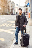 Travel. Handsome young traveler with trolley waiting for the bus. Travel concept Royalty Free Stock Photos