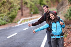 Travel hikers couple hitchhiking on road trip. Travel hikers couple showing thumbs up on street for hitchhiking during road trip. Happy young interracial royalty free stock photo