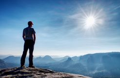 Travel hiking, active vacations in nature. Man at the edge of a cliff. Watch misty landscape stock images