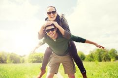 Happy couple with backpacks having fun outdoors. Travel, hiking, backpacking, tourism and people concept - happy couple with backpacks having fun and walking Stock Images