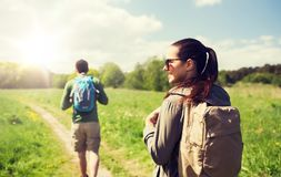Happy couple with backpacks hiking outdoors. Travel, hiking, backpacking, tourism and people concept - happy couple with backpacks walking along country road Royalty Free Stock Images