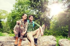Smiling couple with backpacks in nature. Travel, hiking, backpacking, tourism and people concept - smiling couple with backpacks resting and hugging in nature Stock Photo