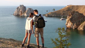 Travel and hiking couple looking at view. People on hike by lake outdoors wearing backpacks trekking in beautiful nature landscape. Active young couple living stock video footage