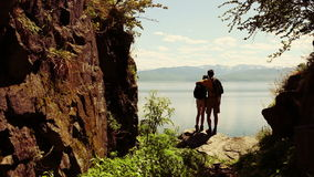 Travel and hiking couple looking at view. People on hike by lake outdoors wearing backpacks trekking in beautiful nature landscape. Active young couple living stock footage