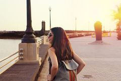 Travel hipster woman with sunglasses and backpack enjoy sunset. Back view of travel girl outdoors with sunset sun flare. Royalty Free Stock Photo