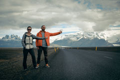 Travel hitchhiker couple on a road Royalty Free Stock Images