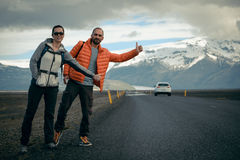 Travel hitchhiker couple on a road Royalty Free Stock Photo