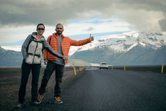 Travel hitchhiker couple on a road. Travel hitchhiker couple walking on road during holiday travel Royalty Free Stock Photo