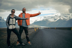 Travel hitchhiker couple on a road. Travel hitchhiker couple walking on road during holiday travel Stock Image