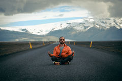 Travel hitchhiker man meditating on a road Royalty Free Stock Photo