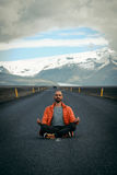 Travel hitchhiker man meditating on a road Royalty Free Stock Image