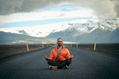 Travel hitchhiker man meditating on a road Royalty Free Stock Photography