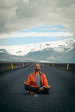 Travel hitchhiker man meditating on a road. Travel hitchhiker man on a road during holiday travel Royalty Free Stock Images