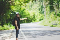 Hitchhiker woman with hat and backpack walking on a road Royalty Free Stock Image