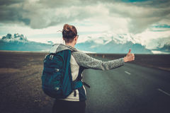 Travel hitchhiker woman walking on a road Stock Photos