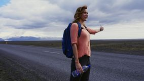 Travel hitchhiker woman walking on a road stock footage