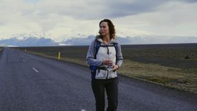 Travel hitchhiker woman walking on a road. Travel hitchhiker woman walking on road during holiday travel stock footage