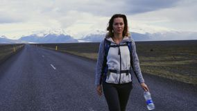 Travel hitchhiker woman walking on a road. Travel hitchhiker woman walking on road during holiday travel stock video footage