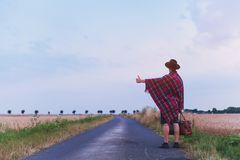 Travel by hitchhiking, hitchhiker backpacker on the road. Travel by hitchhiking, hitchhiker backpacker standing  on the road Royalty Free Stock Images