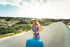 Travel, holiday, summer and vacation concept - Young charming woman is standing and laughing on road with suitcases Royalty Free Stock Photo