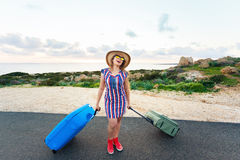 Travel, holiday, summer and vacation concept - Young woman is standing and laughing on road with suitcases Royalty Free Stock Photos