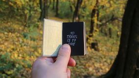 Travel holiday tourism vacation idea. Hand holding a book with the inscription on the background of autumn forest stock footage