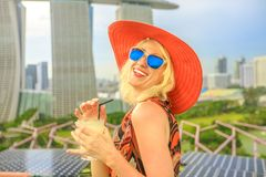 Singapore woman aperitif. Travel holiday vacation in Singapore, Southeast Asia. Lifestyle caucasian woman with wide hat drinking aperitif at rooftop. Aerial view royalty free stock photo