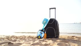 Travel holiday vacation suitcase with cream, straw hat and diving mask on the beautiful beach. Advertisement on travel. Suitcase stock video