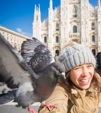 Travel, holidays and winter vacations concept - Happy young woman take selfie photo with funny pigeons in front of Duomo royalty free stock photo