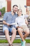 Travel Ideas and Concepts. Young Caucasian Couple in Love Sitting Embraced Stock Photos