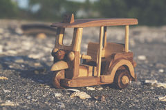 Travel image concept, wooden miniature tuk-tuk, most iconic Thailand transportation over beach background Stock Photo